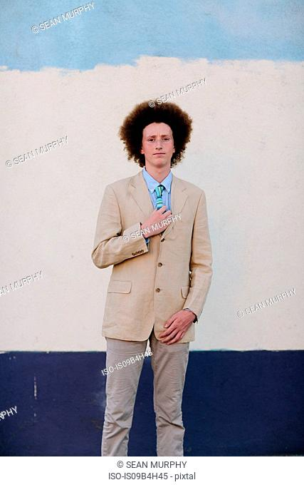 Portrait of teenage boy with red afro hair, wearing suit, outdoors