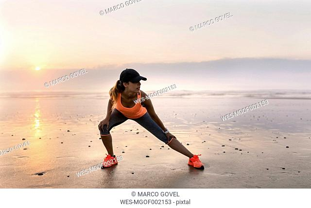 Young athlete woman doing stretching on the beach at sunset