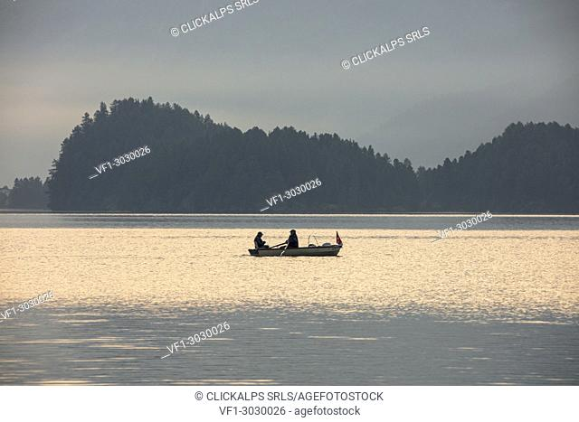 Fishermen in the calm water of Lake Sils at sunrise, Plaun da Lej, canton of Graubunden, Engadine. Switzerland