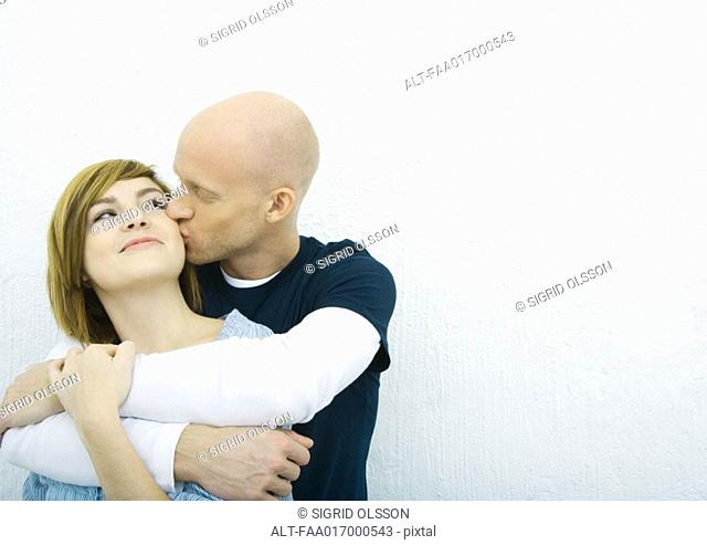 Young couple, man kissing woman's cheek woman from behind