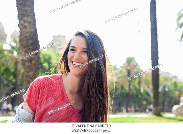 Happy young woman in park, portrait