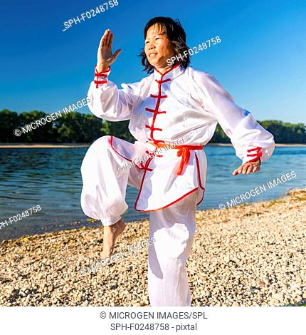 Women practicing tai chi by a lake