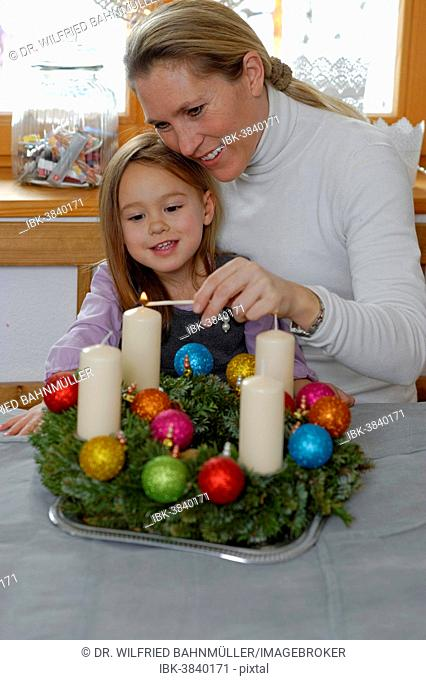 Mother and daughter lighting the first candle on the Advent wreath, first Sunday in Advent