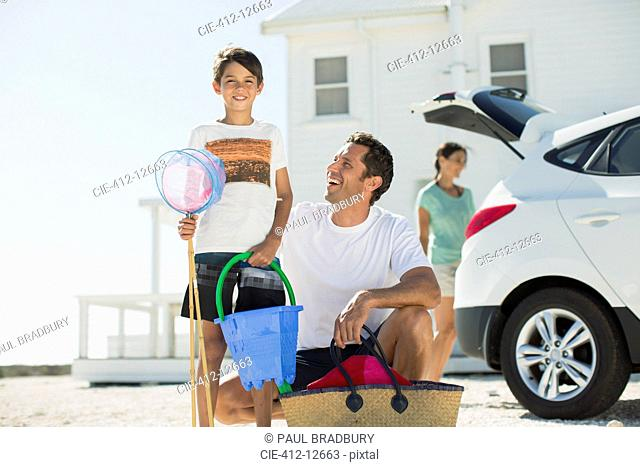 Father and son holding beach gear outside car in sunny driveway