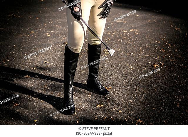 Woman wearing riding boots, holding riding crop, low section