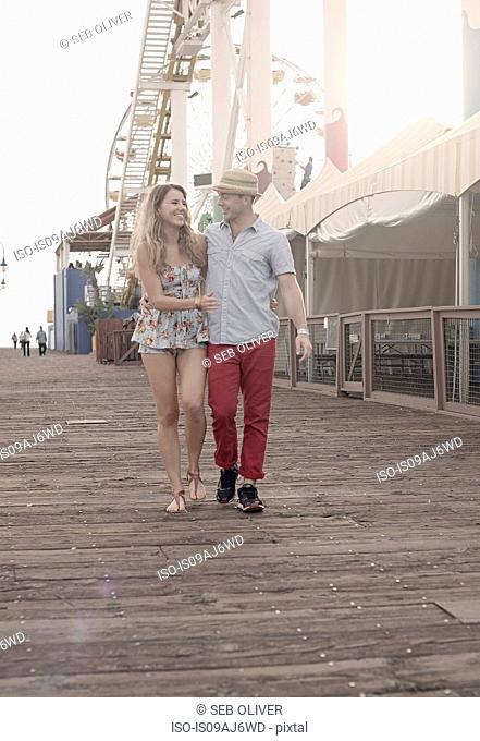 Young couple strolling on Santa Monica pier, California, USA