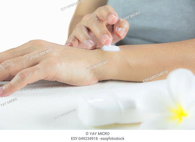 hand of woman apply lotion on skin of her arm with lotion bottle isolated on white background
