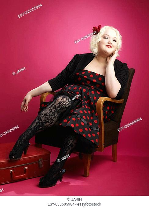 Flirting pin-up girl sitting on old retro chair and she looks toward the camera, pink background