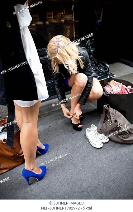 Woman changing trainers for high heels