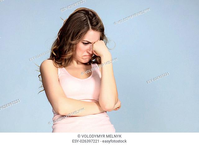 The portrait of a beautiful sad girl closeup on gray