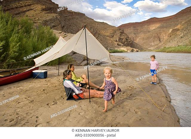 Two young girls playing near their mothers while camping on the San Juan River, Mexican Hat, Utah