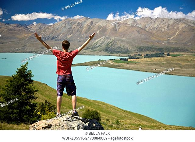 A young man looks out over Lake Tekapo, South Island, New Zealand, Model Released