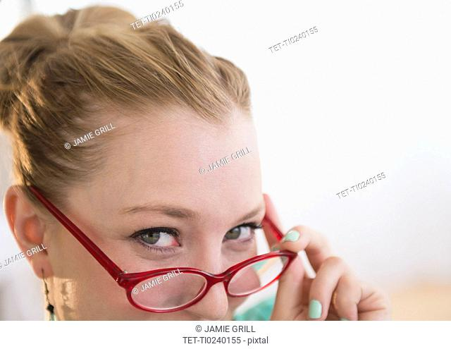 Portrait of smiling young woman peeking through glasses