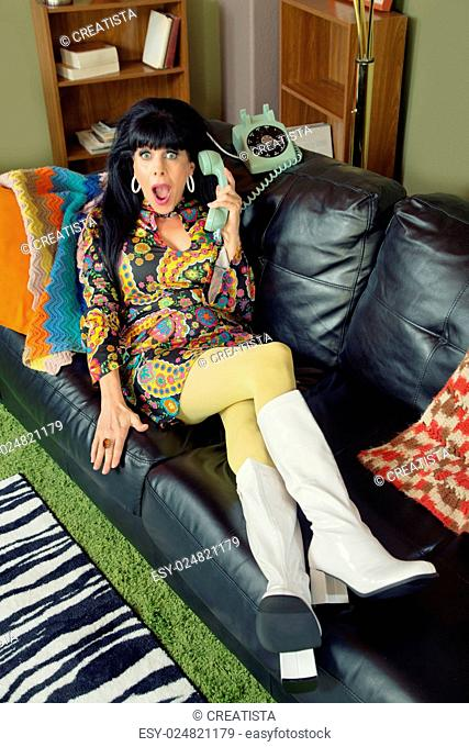 Amazed pretty woman on sofa holding telephone