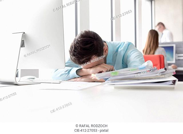Frustrated businessman with head down next to stack of reports on desk