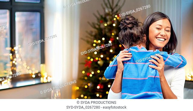 happy mother hugging her daughter on christmas