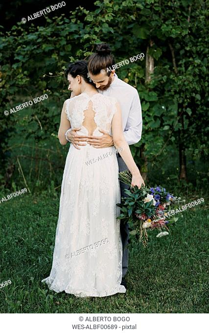 Bride and groom standing on meadow embracing