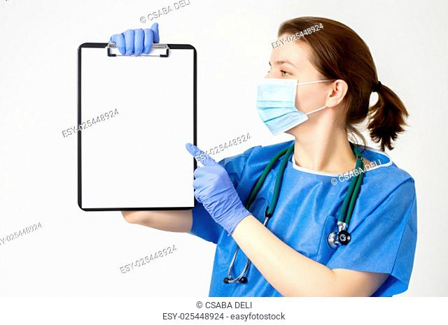 Female doctor pointing at a clipboard with blank paper