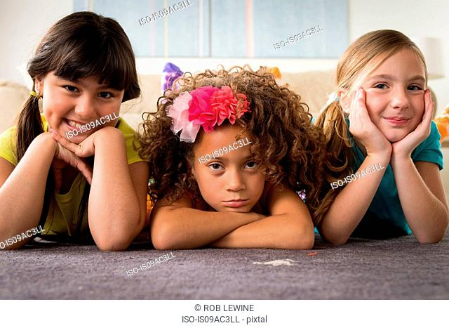 Portrait of three girls lying on front