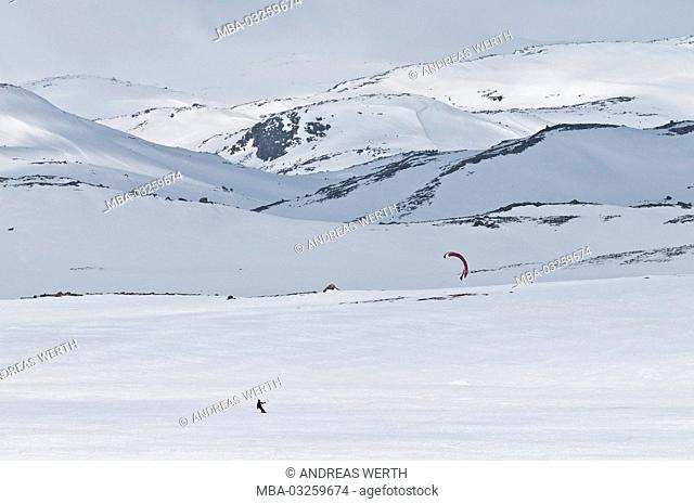 Kitesailing on frozen lake Örteren, plateau Hardangervidda, approx. 30 km to the west of the place Geilo, winter, snow-covered mountain landscape, Buskerud