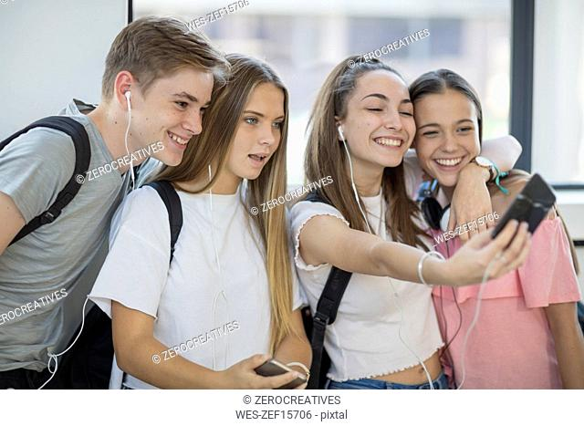Happy students taking a selfie in school