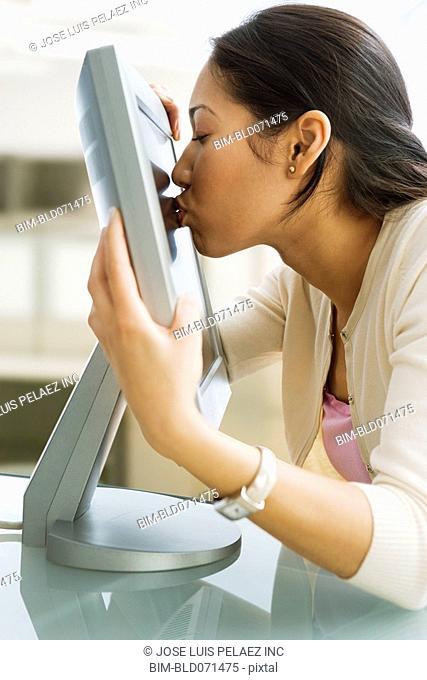 Pacific Islander businesswoman kissing computer monitor