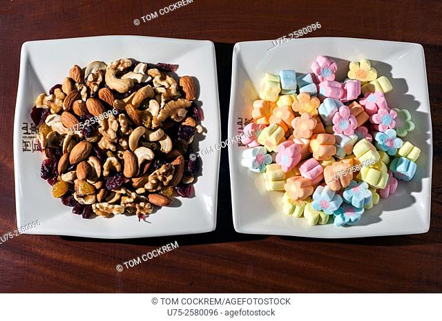 Bowl of nuts and dried fruit alongside bowl of marshmallows in studio setting
