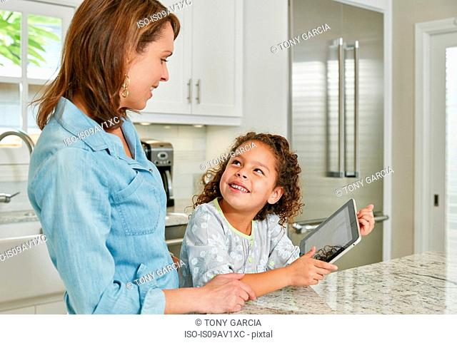 Mother and daughter at kitchen counter using digital tablet, looking up smiling