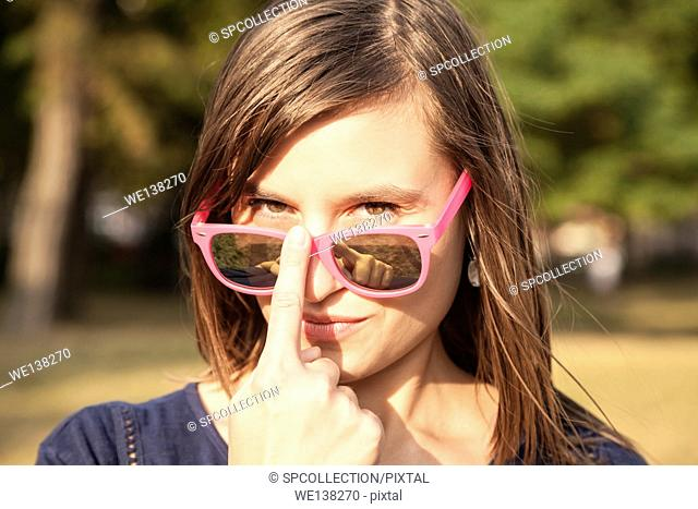 Attractive woman looking over sunglasses