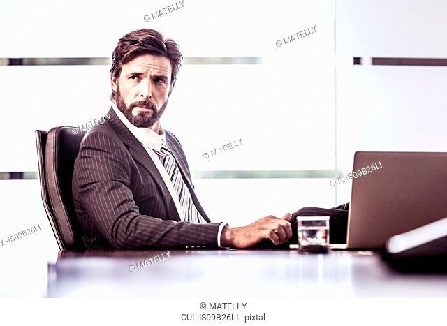 Confident businessman looking over shoulder from office desk
