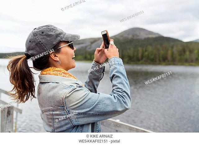 Finland, Lapland, happy woman on jetty at a lake taking a selfie