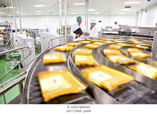Workers talking behind packages of cheese moving on conveyor belt in processing plant