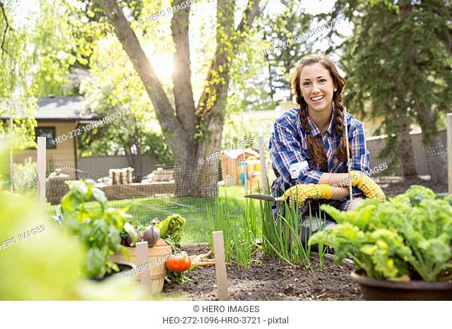 Portrait of smiling woman in vegetable garden