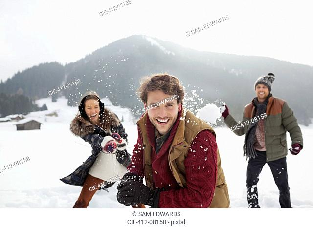 Portrait of playful friends throwing snowballs in field
