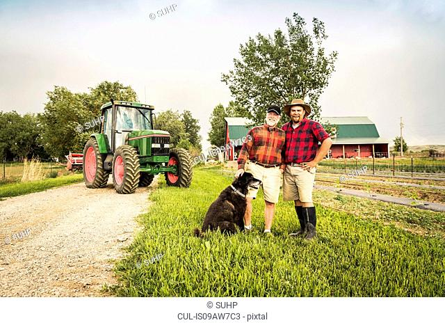 Father and son with dog on farm in front of tractor looking at camera smiling