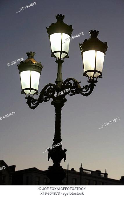 illuminated old fashioned street lamp at dusk on oconnell bridge Dublin, Republic of Ireland