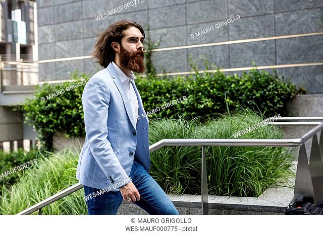 Stylish businessman walking on stairs outdoors