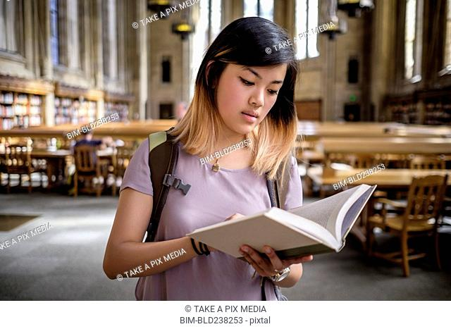 Chinese woman standing in library reading book