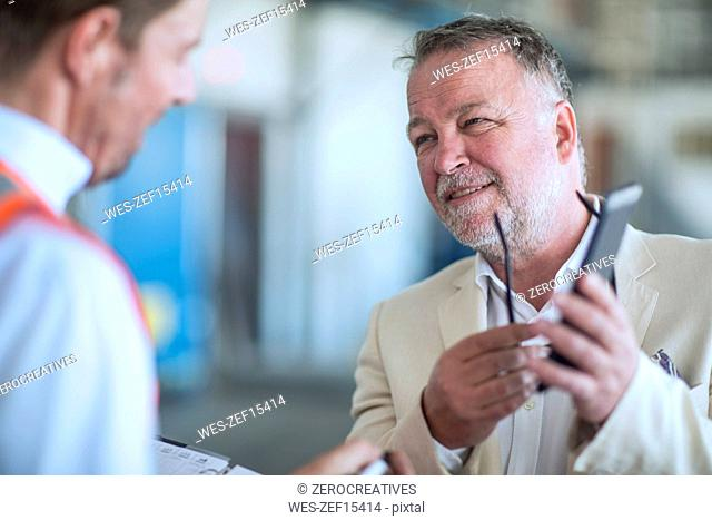 Businessman showing cell phone to man in reflective vest in industrial hall