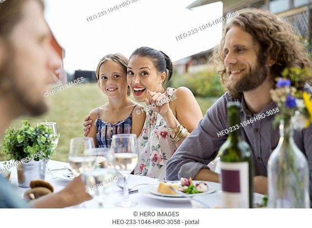 Woman and young girl at outdoor dinner party pointing at camera