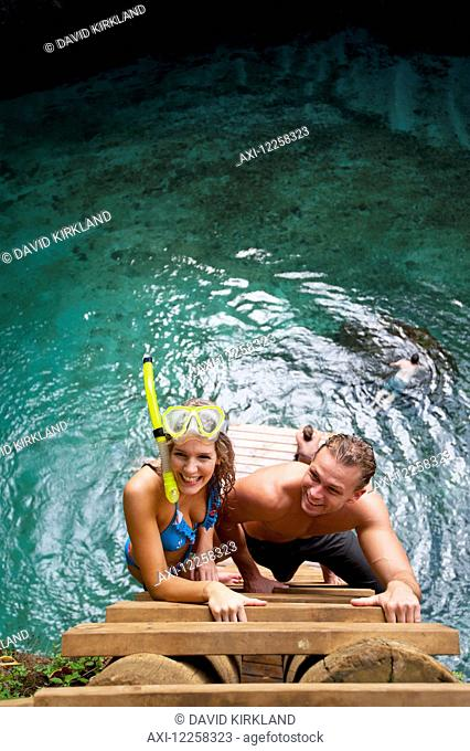 Couple climbing the ladder from To Sua trench; Upulu Island, Samoa