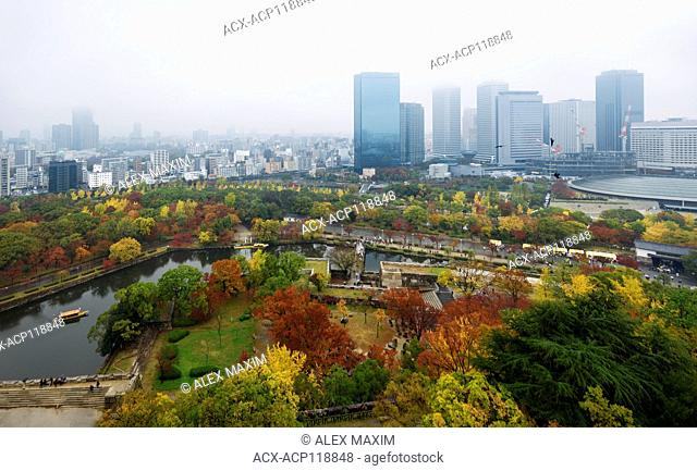 Osaka Castle Park and Chuo-ku financial distric city skyline aerial view with tourist boats and Gokurakubashi bridge on inner moat canal on a misty autumn...