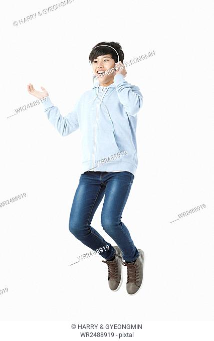 Smiling school boy in casual clothes jumping listening to music
