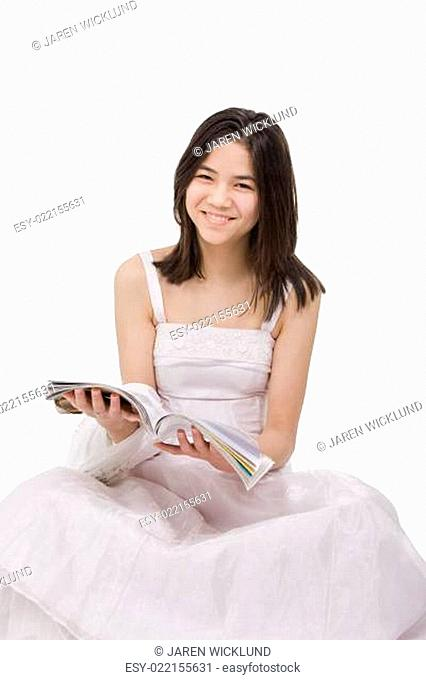 Beautiful young teen girl in white dress sitting reading a magazine