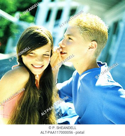 Boy whispering to girl standing side by side