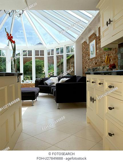 View from kitchen of white ceramic tiled floor and black sofa in modern conservatory extension