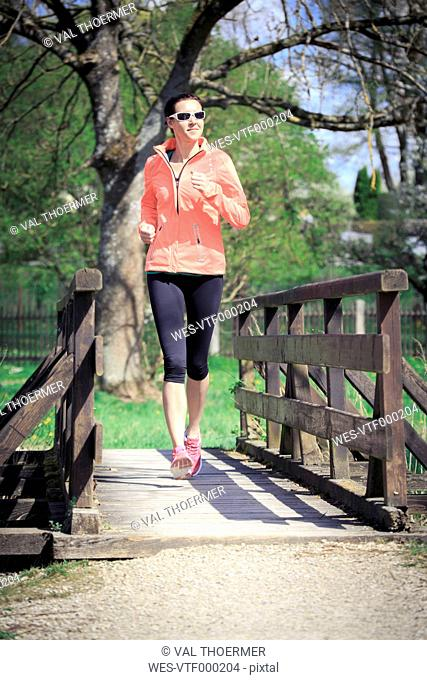 Woman jogging over a footbridge