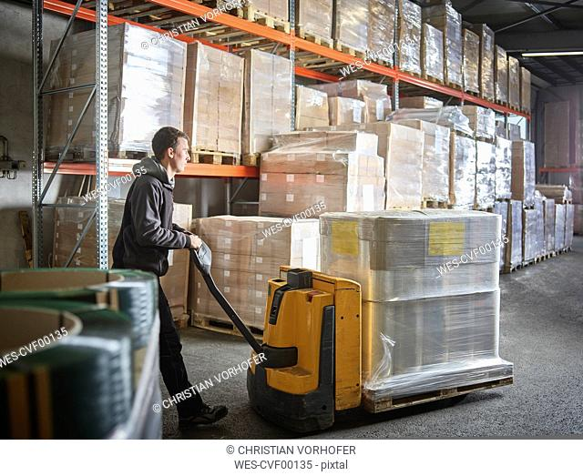 Man operating pallet jack in storehouse