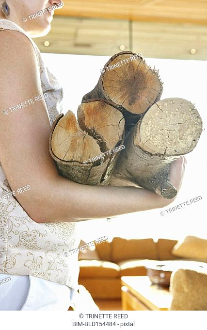Close up of woman carrying firewood logs
