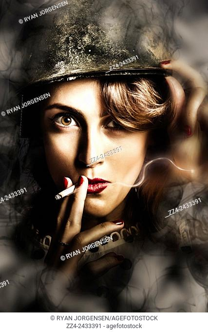 Dramatic and tense headshot of a smoking hot female soldier inhaling cigarette ration in dark atmospheric winter twilight. Night watch military pin up